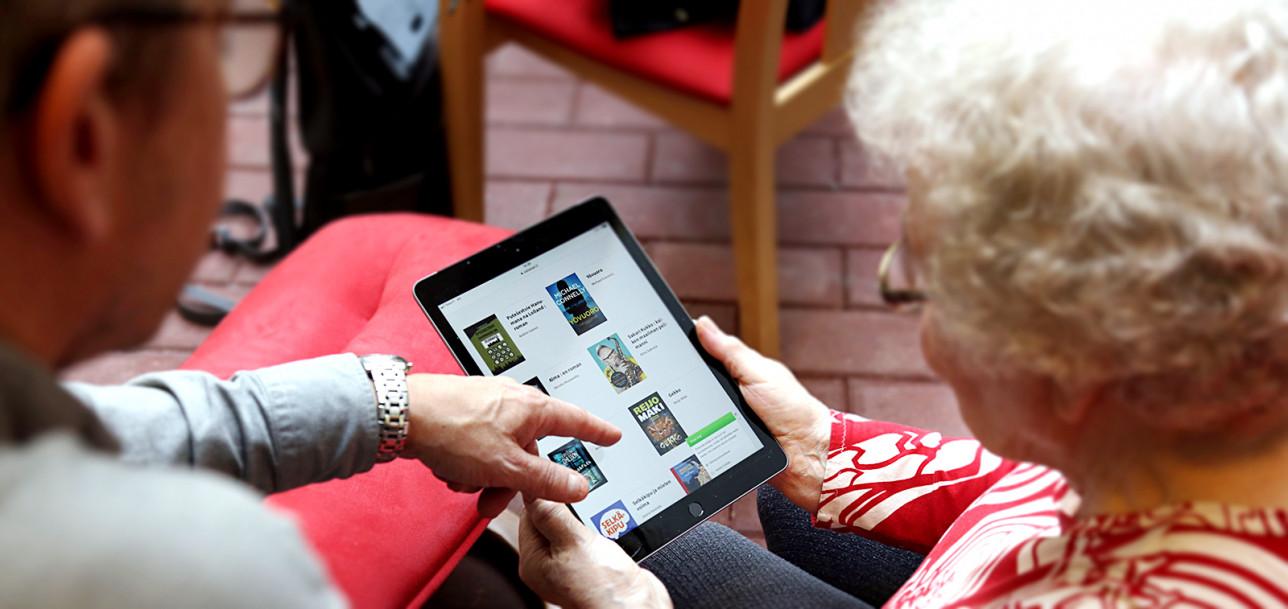 Vanhempi nainen pitää tablet-laitetta ja toinen opastaa sen käytössä.