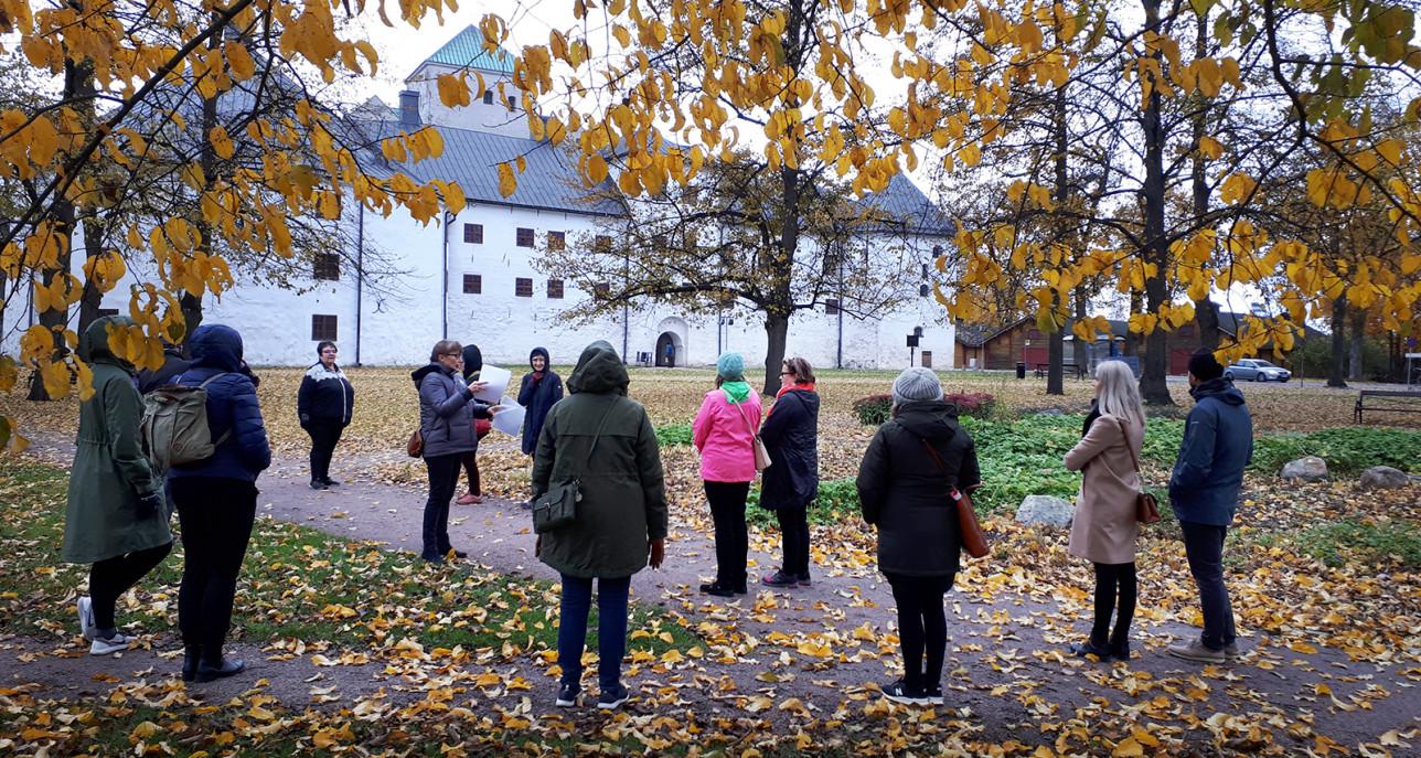 Ryhmä ihmisiä kuuntelee oppaan esitystä Turun linnan luona.