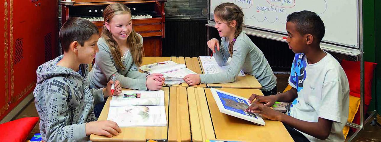 Neljä koululaista istuu pulpeteillaan