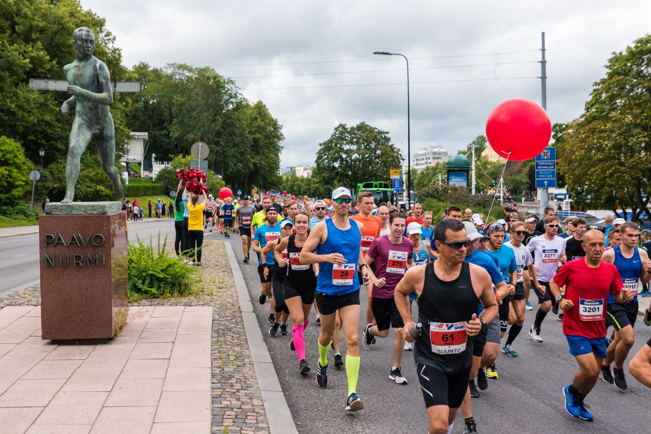 Maratonjuoksijoita ohittamassa Paavo Nurmen patsasta.