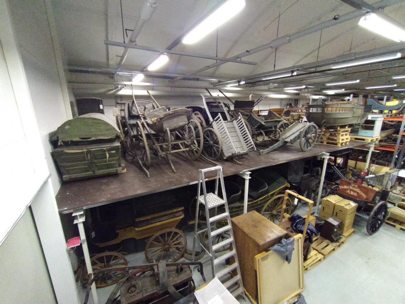 Hevosvetoisia vaunuja säilössä varastotilassa kahdessa eri tasossa. Kuvassa myös tikapuut.