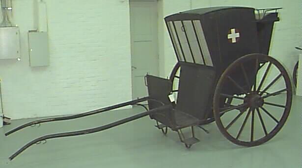 Mustat kuomulliset sairaankuljetusvaunut, joissa on isot pyörät