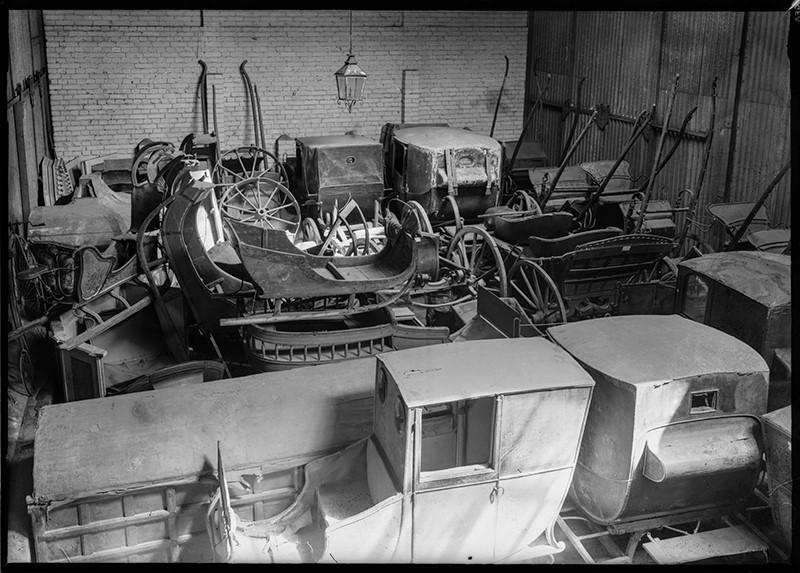 Vaunuja ja kärrynpyöriä varastossa, jossa on tiiliseinä