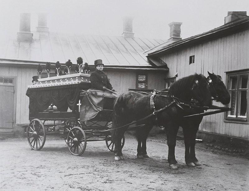 Kaksi mustaa hevosta seisoo mustien ruumisvaunujen edessä. Silinterihattuinen ajuri istuu kuskinpukilla.