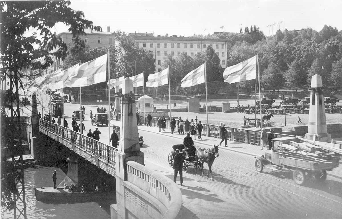 Hevosvaunuja, käveleviä ihmisiä ja avolavainen kuorma-auto Aurasillalla Turussa. Suomenliput liehuvat sillan kaiteissa.