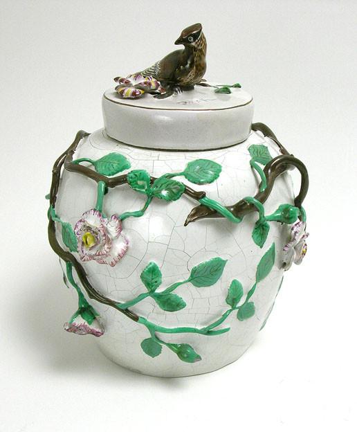 korkea valkoinen ruukku, jonka ympärillä keraamista vihreää ruusuköynnöstä vaaleanpunaisine ruusuineen. Ruukun kannen päällä keraaminen pieni lintu