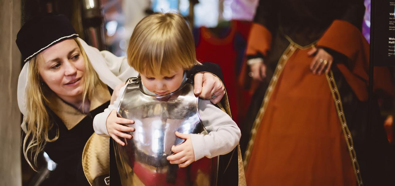 Pikkuritari pukeutuu haarniskaan Turun linnan Ritarisalissa