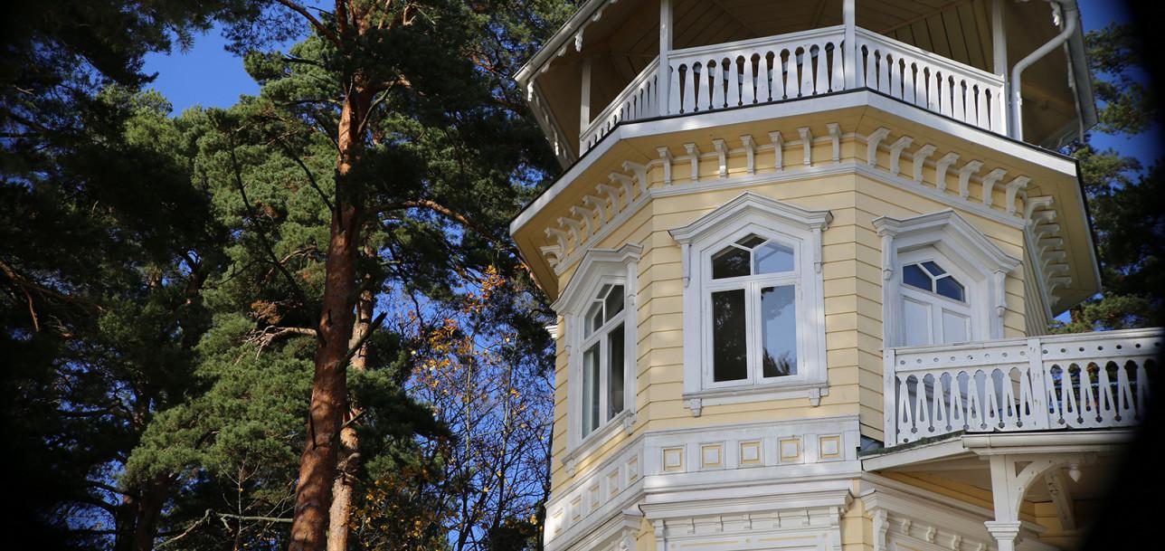 Huvilan vaalea torniosa, jossa on pieniä ikkunoita.