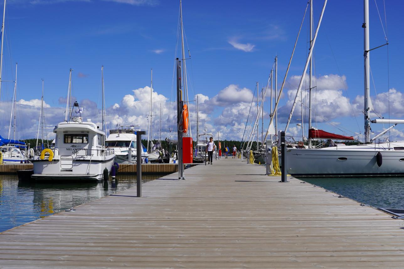 Purjeveneitä venelaiturissa, sininen taivas, valkoisia veneitä ja laituri