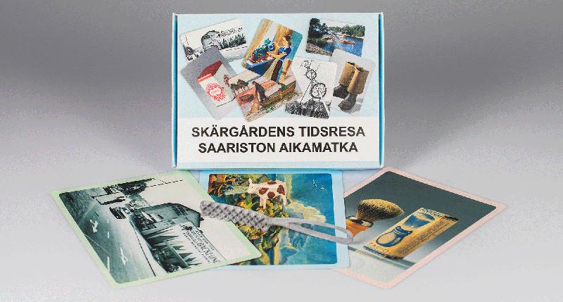 Vaaleansinisen laatikon edessä kuvakortteja, suomustusrauta ja pieni leikkilehmä. Laatikossa lukee Skärgårdens tidsresa – Saariston aikamatka.