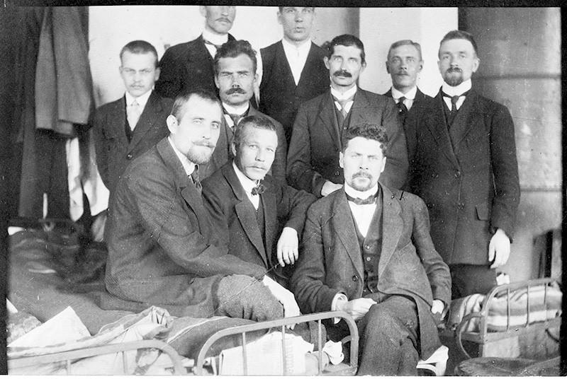 Vankeja Sirkkalan kasarmilla. Kymmenestä miehestä osa istuu sängyllä ja tuolilla sekä osa seisoo.