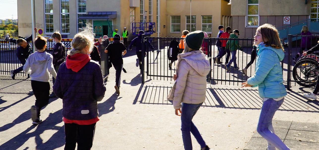 Sirkkalan koulun oppilaita juoksemassa kohti koulurakennusta