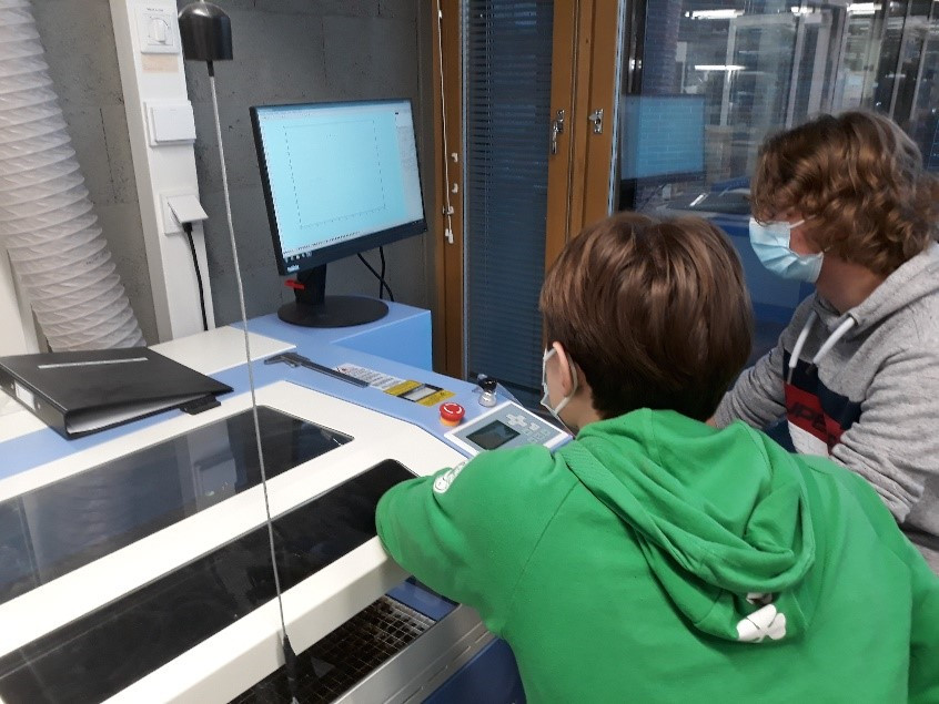 Kaksi Syvälahden oppilasta laboratoriolaitteen vierellä seuraamassa tuloksien ilmestymistä näytölle.