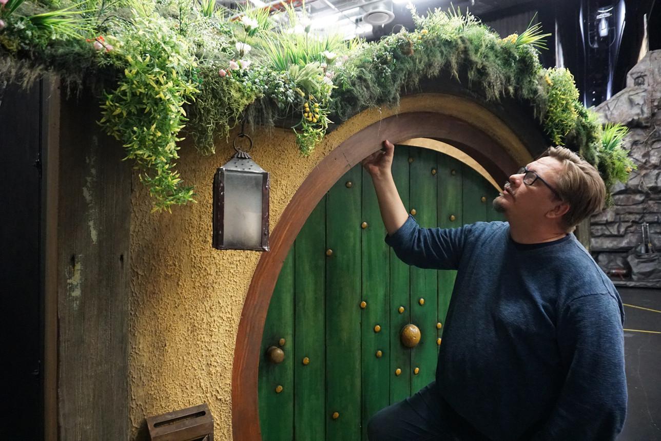 Mies astumassa sisään pyöreästä vihreästä ovesta
