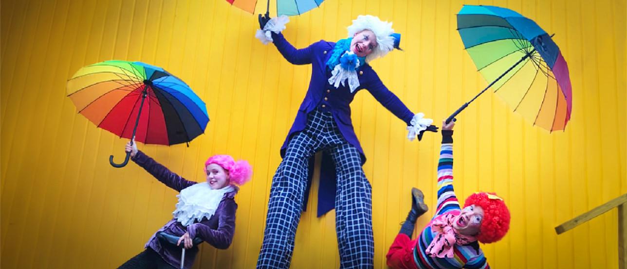 Kolme sirkushahmoa värikkäissä vaatteissa