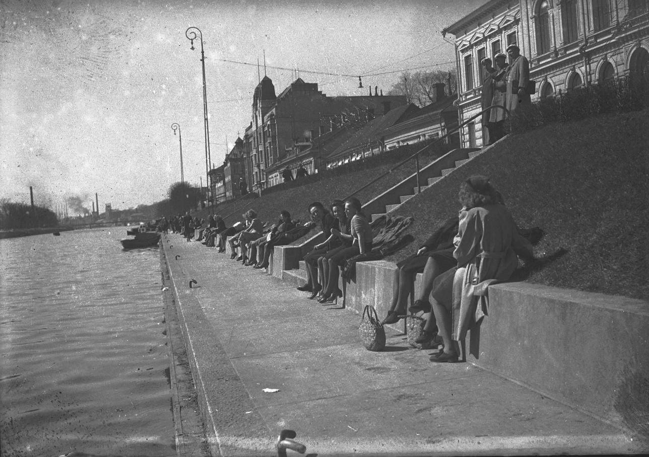 Ihmisiä istuskelee auringossa joen rannalla