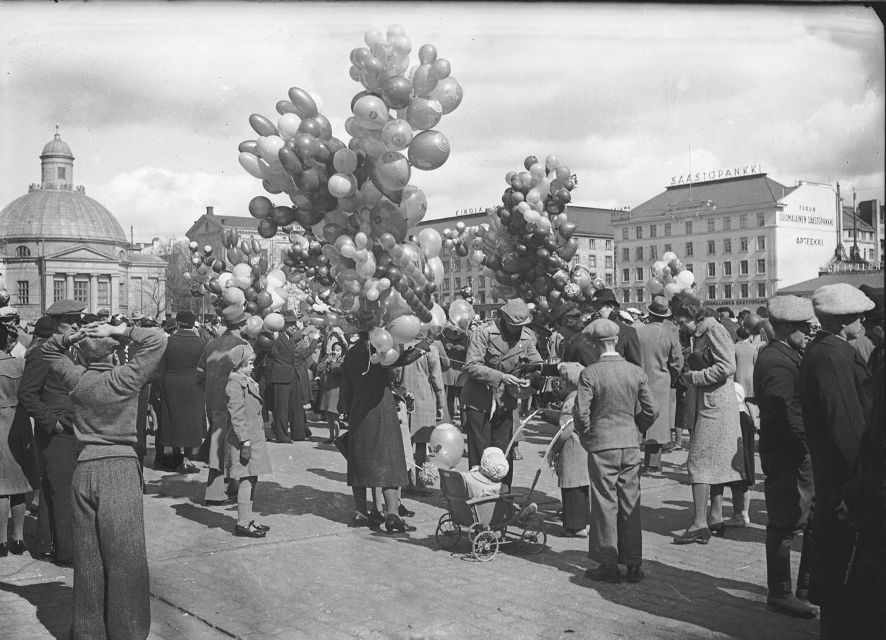Myyjät pitelevät ilmapallokimppuja torilla