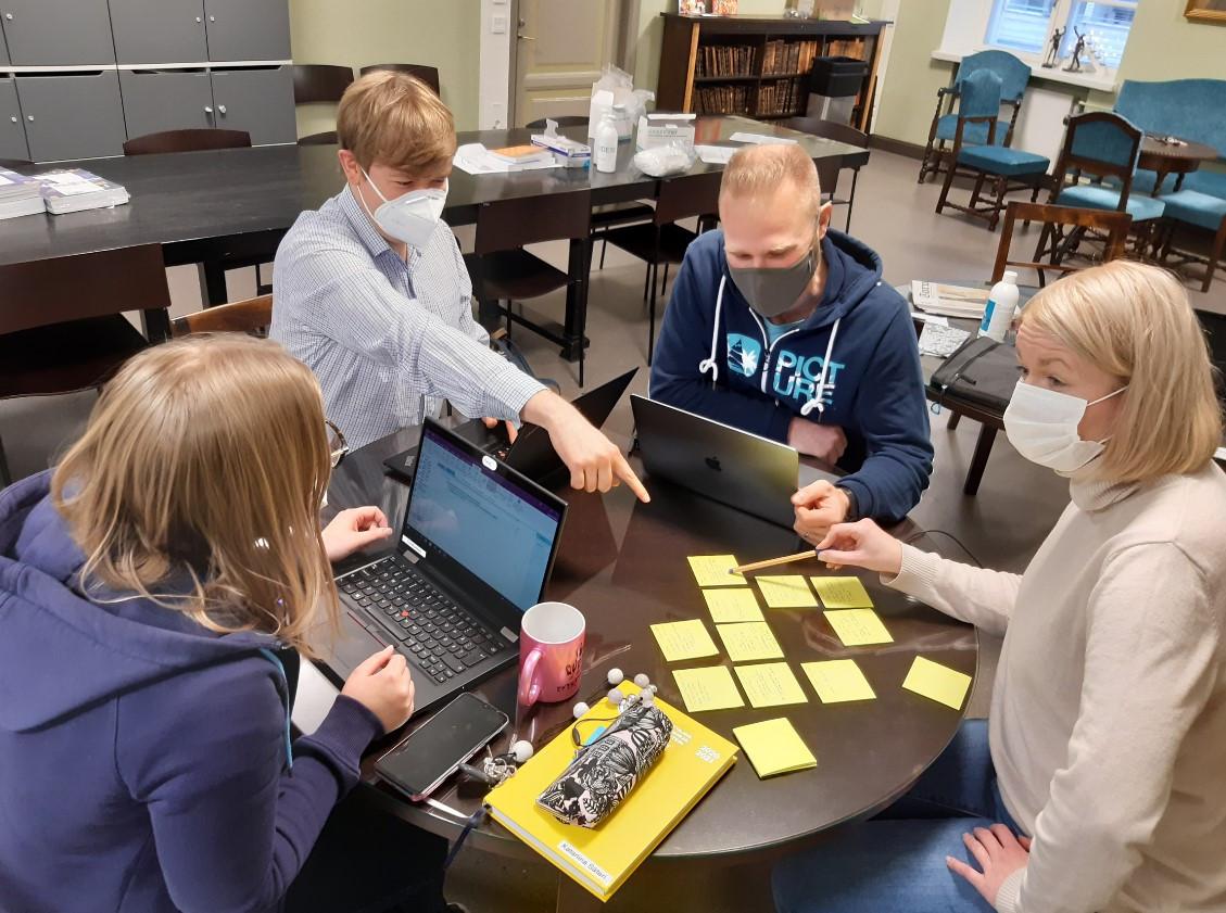 Turun Suomalaisen Yhteiskoulun lukion opettajat istuvat pöydän ääressä suunnittelutyössä.