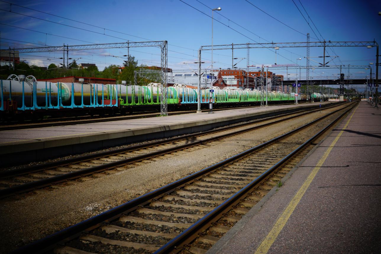 Raitiotietä, taustalla juna ohittamassa asemaa