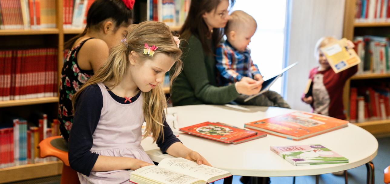 Muutama lapsi istuu kirjaston lastenosastolla pyöreän pöydän ääressä lukemassa kirjoja