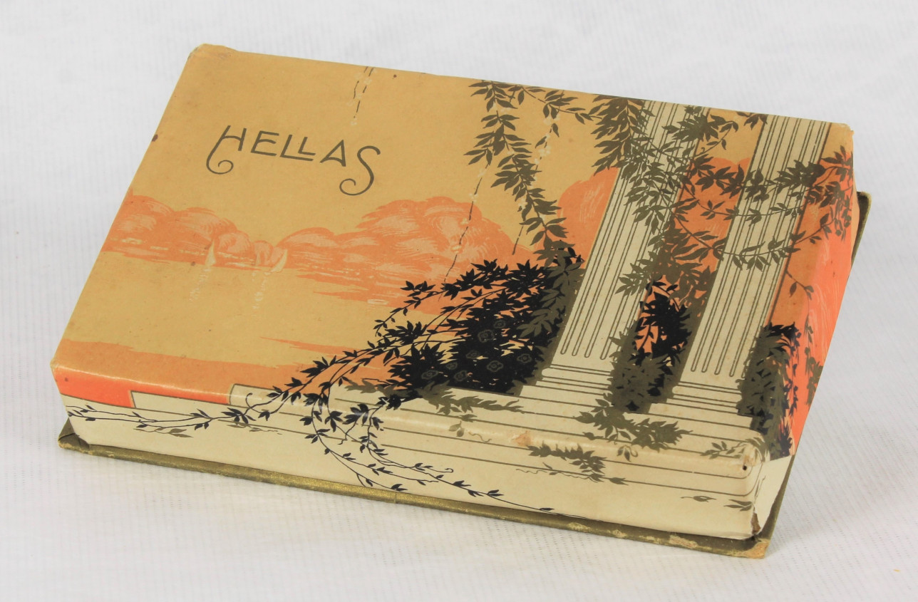 Suorakaiteen muotoinen pahvinen suklaarasia, jonka kannessa on kaksi valkoista pylvästä ja portaat, joissa luikertelee kasveja. Taustalla on oranssisävyinen merimaisema.