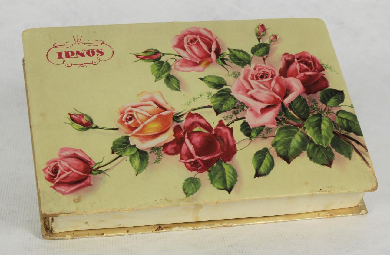 Pahvinen suorakaiteen muotoinen suklaarasia, jonka kannessa on kuva ruusukimpusta.