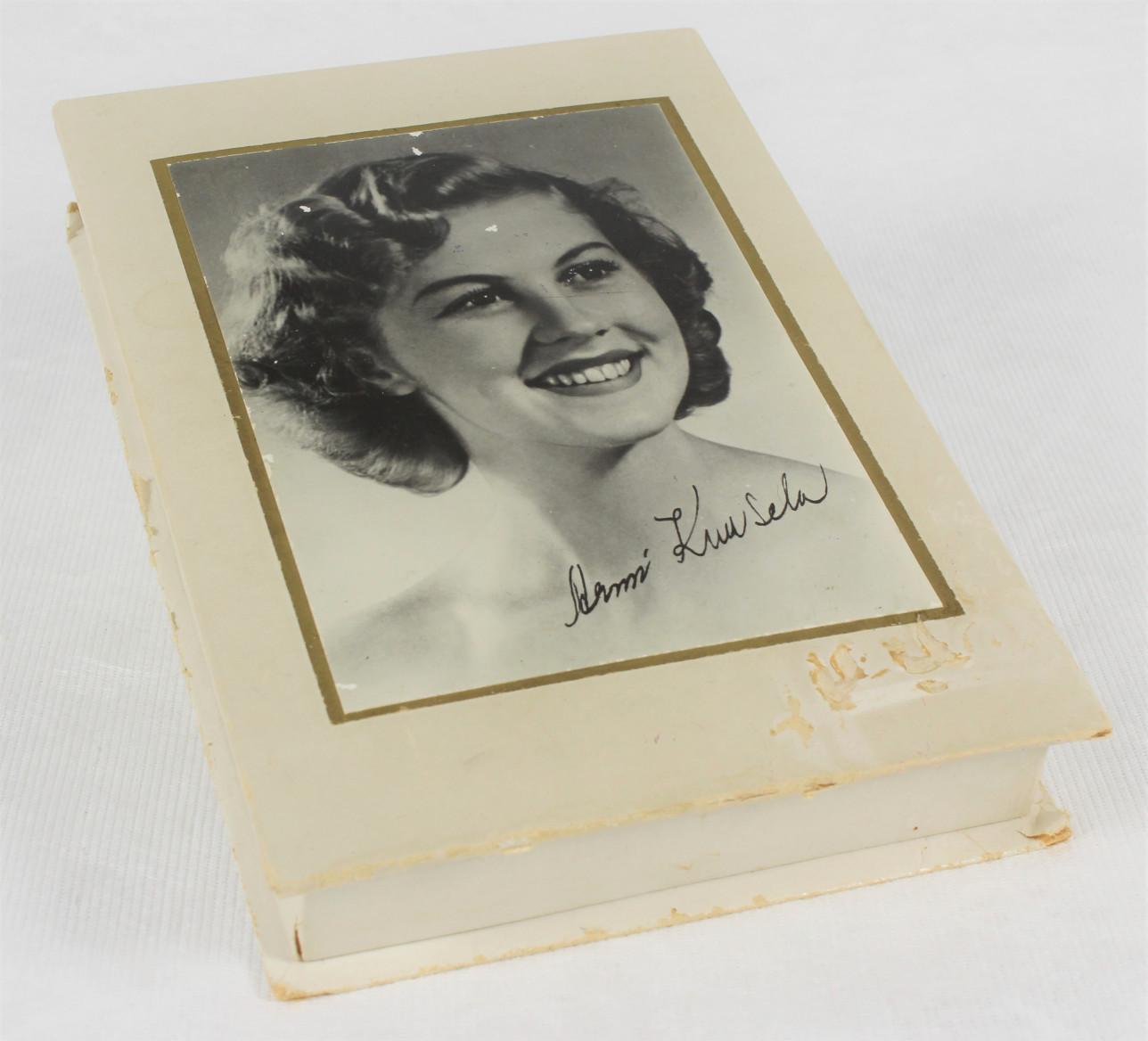 Valkoinen pahvinen suklaarasia, jonka kannessa on kuva Armi Kuuselasta. Kuvassa on myös Armi Kuuselan nimikirjoitus.