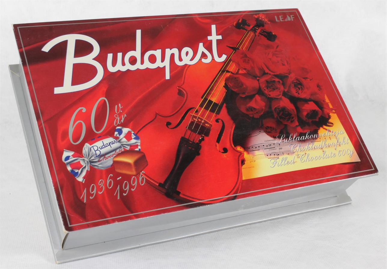 Suorakaiteen muotoinen pahvinen rasia, jonka kannessa on punaisella kankaalla viulu, ruusukimppu ja kuva Budapest makeisesta sekä merkintä 60 v år 1936–1996.