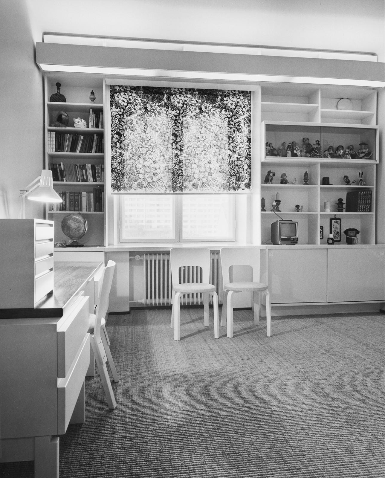 Kuvan vasemmassa reunassa työpöytä ja lamppu. Edessa ikkuna missä kukkakuvioinen kaihdinverho. Ikkunaa ympäröi molemmin puolin koko seinän kokoinen hyllykkö. Vasemmalla puolella hyllyssä kirjoja ja karttapallo, oikealla puolella ylähyllyllä nukkeja.