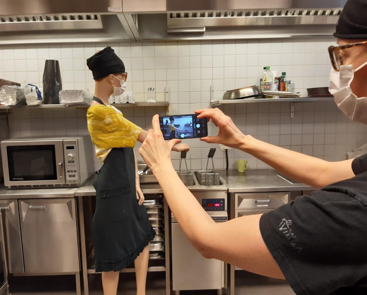 Kahvilatyöntekijä kuvaa kokiksi aseteltua mallinukkea keittiössä.