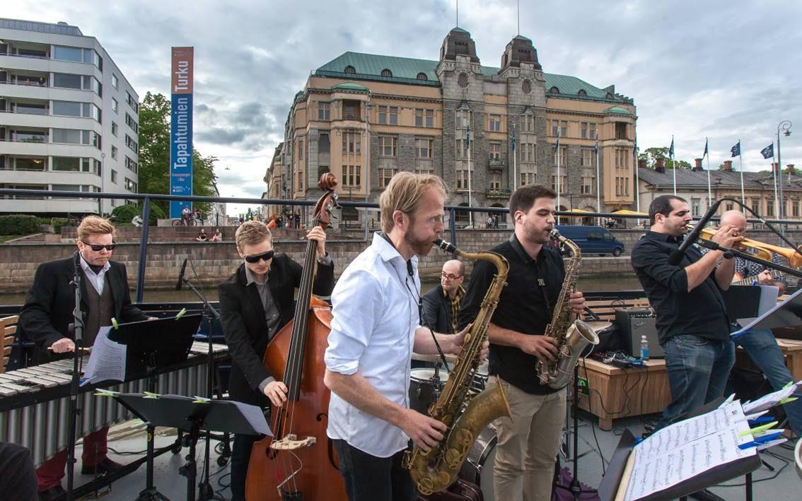 Seitsemän jazzmuusiikkoa soittamassa Aurajoen rannalla. Kuvassa mm. saksofoneja.