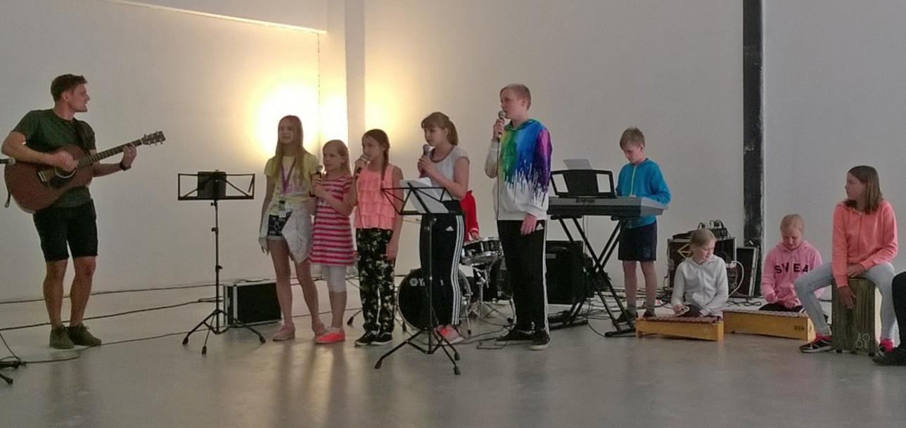 Moision koulun bändi esiintyy opettajan johdolla