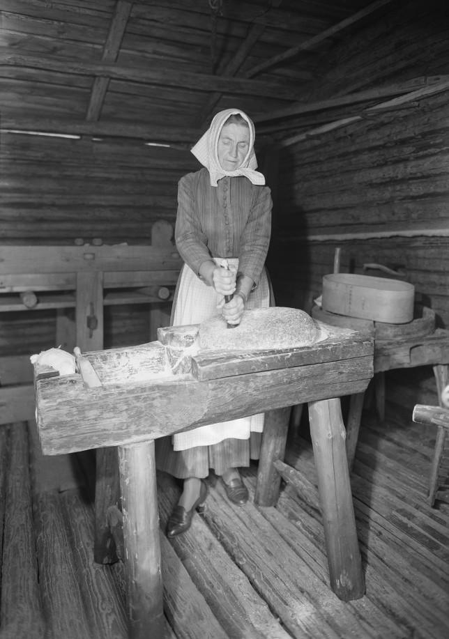 Hilma Mäenpää jauhaa käsikivillä Luostarinmäen tapahtumassa v. 1963.