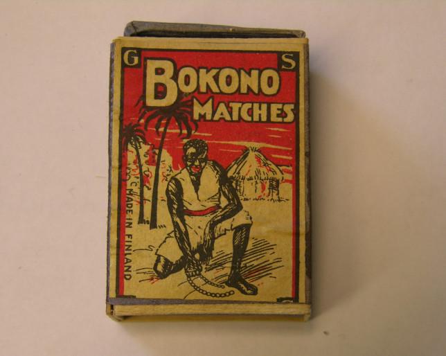 Bokono-tulitukkujen rasia, jossa tummaihoinen mies esitetty alkuasukkaana, taustalla maja.