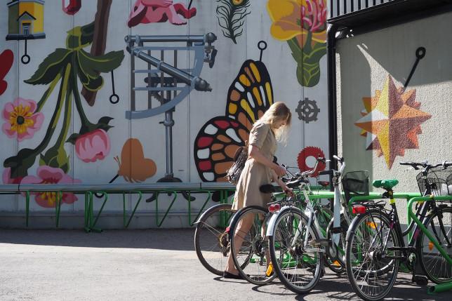 Nuori nainen pysäköi pyöränsä pyörätelineeseen.