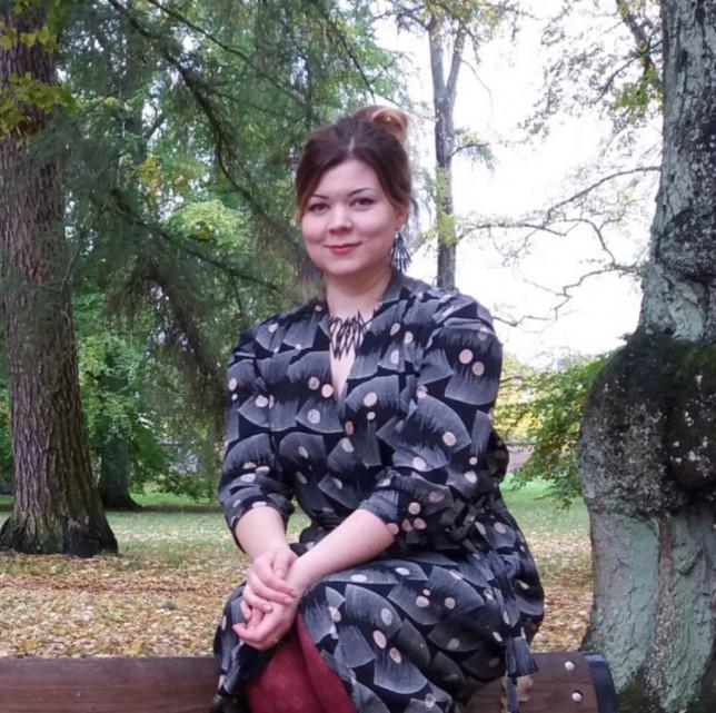 Jutun kirjoittaja Elina Maannitty istuu puistonpenkin selkänojalla.