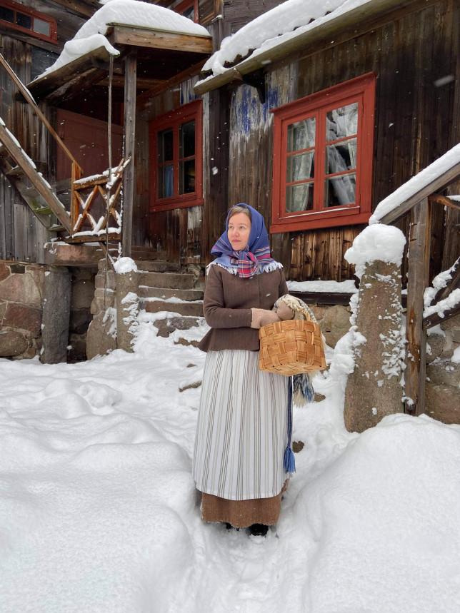 Aikauden asuun pukeutunut nainen Luostarinmäen pihapiirissä