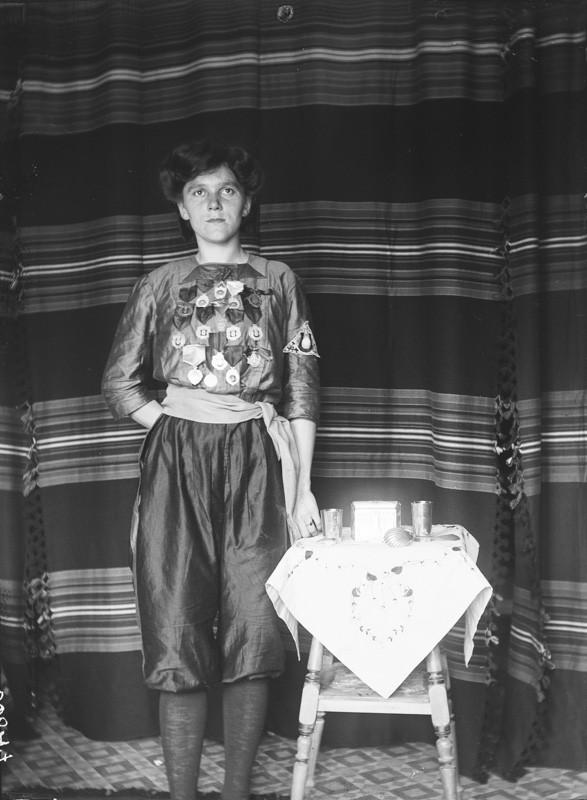 Nuoren näköinen Lizzie Nyström totisena seisomassa kuvassa vaakaraitaisen verhon edessä. Hänen vierelleen on aseteltu liinalla peitetty pikkupöytä, jonka päällä on palkintolusikka ja pokaaleja.
