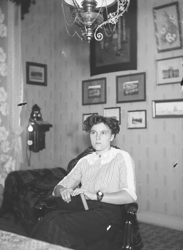 Nuori nainen, Lisie istuu tuolilla kirja kädessään vakavailmeisenä.