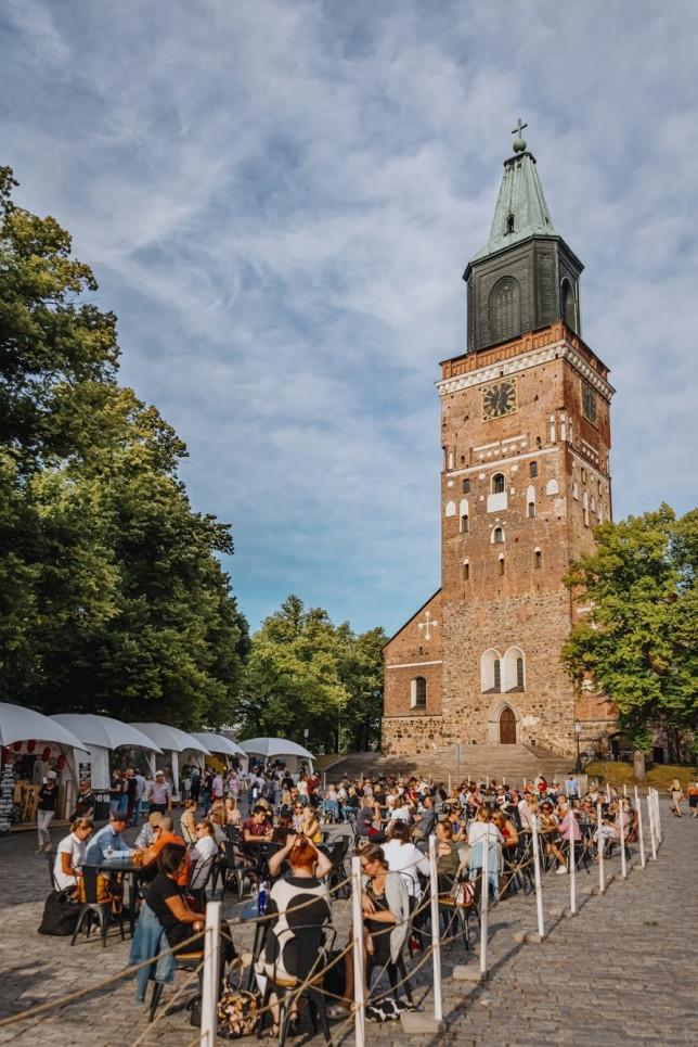 Turun tuomiokirkko ja sen edustalla terassialue, jonka pöydissä istuu ihmisiä.