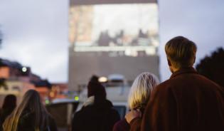 Ihmisiä katsomassa ulkoilmaelokuvaa talon seinästä.