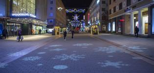 Lumihiutaleet-valoteos heijastettuna kävelykadun pintaan.
