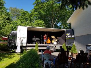 Neljä muusikkoa soittaa jazzia kuorma-auton lavalla kesäisellä pihalla.