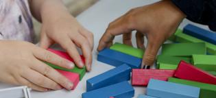 Aikuisen ja lapsen kädet kokoavat rakennuspalikoita.
