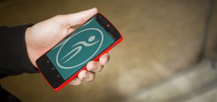 Ihmisen kädessä oleva älypuhelin, jonka näytöllä Täsä-mobiilisovelluksen logo