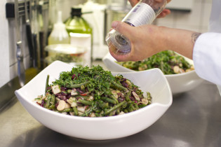 Kokki murskaa mausteita ruoka-annoksen päälle