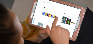 Henkilö käyttää Åbok-verkkopalvelua tabletilla