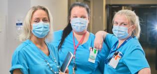 Hoitajat seisovat rivissä työvaatteissaan