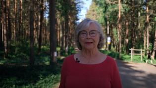 Nainen kävelee metsäpolulla