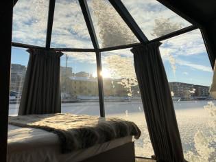 AuroraHutin vuode ja ikkunoista näkyvät talviset Aurajoki-maisemat.